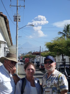 Jeff,John and Dee with the volcano behind them that has just erupted showing its huge plume of ash