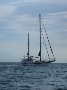 Sailing Vessel Vagabond under power from their dinghy,lashed on port side