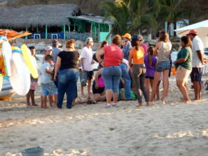 The Jefe laying down on the beach being helped in Chamela, Mexico